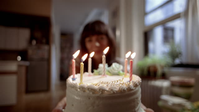 ms woman pushing birthday cake w/ candles toward camera/ man leaning in + blowing out candles/ new york city - birthday cake stock videos & royalty-free footage
