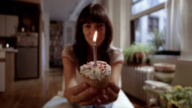 vídeos de stock e filmes b-roll de ms woman pushing birthday cupcake w/ candle toward camera/ man leaning in + blowing out candle/ new york city - soprar
