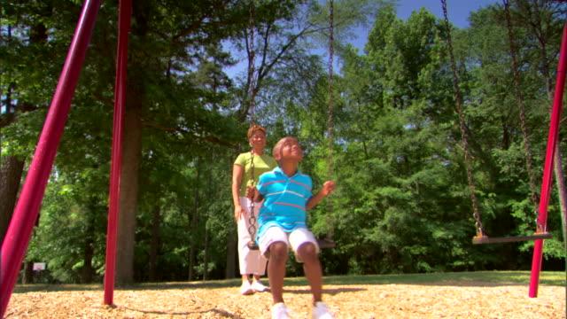 woman pushing boy on a swing - この撮影のクリップをもっと見る 1278点の映像素材/bロール