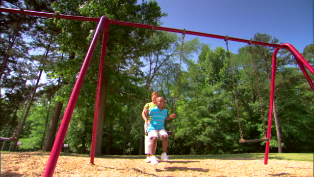 woman pushing boy on a swing - kinderspielplatz stock-videos und b-roll-filmmaterial