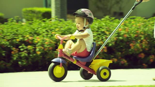 ms pan woman pushing boy (2-3) on tricycle, followed by man / burbank, california, usa  - fahrzeug fahren stock-videos und b-roll-filmmaterial