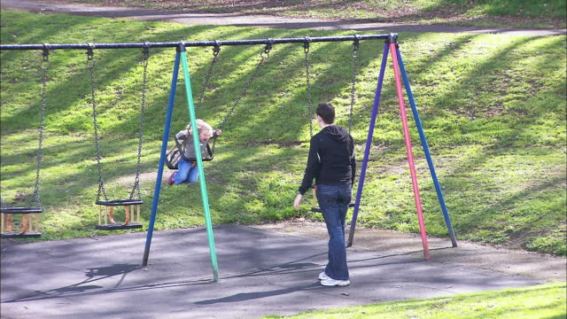 woman pushing child on swing, northern ireland - pushing stock videos and b-roll footage