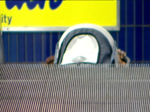 vídeos de stock e filmes b-roll de woman pushing child's buggy alights from escalator of u-bahn underground station munich - escada rolante