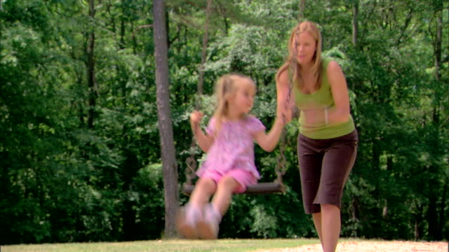 woman pushing girl on a swing - see other clips from this shoot 1428 stock videos & royalty-free footage