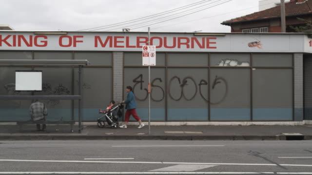 WS Woman pushing pram down sidewalk in low income neighborhood, Melbourne, Victoria, Australia