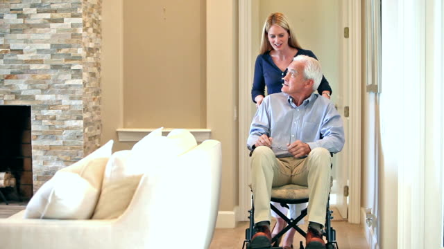 woman pushing senior man in wheelchair at home - adult offspring stock videos & royalty-free footage