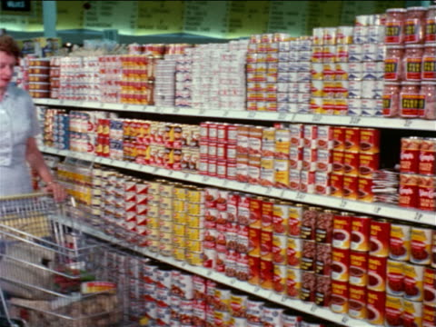 stockvideo's en b-roll-footage met 1964 woman pushing shopping cart stops in canned food aisle of grocery store / educational - prelinger archief