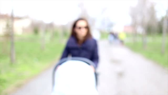 woman pushing stroller with baby - unknown gender stock videos & royalty-free footage