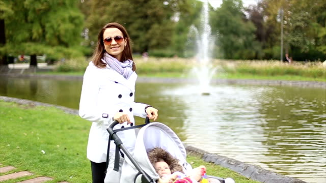 woman pushing stroller with baby - three wheeled pushchair stock videos & royalty-free footage