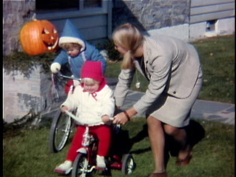 stockvideo's en b-roll-footage met 1963 ms composite woman pushing two daughters on bicycle and tricycle, vermont, usa - 1963