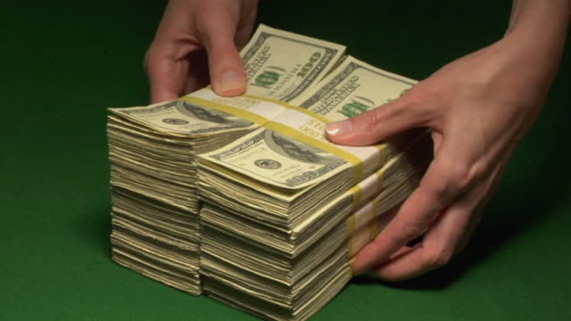 CU, Woman pushing two stacks of American dollar bills in paper bands on table, close-up of hands