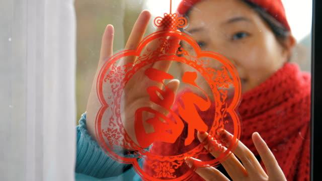 vídeos de stock e filmes b-roll de woman put on chinese traditional paper-cut on window - ano novo chinês