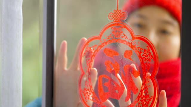 woman put on chinese traditional paper-cut on window - chinese new year stock videos & royalty-free footage