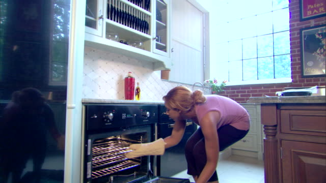a woman puts a frozen dinner in the oven. - oven mitt stock videos and b-roll footage