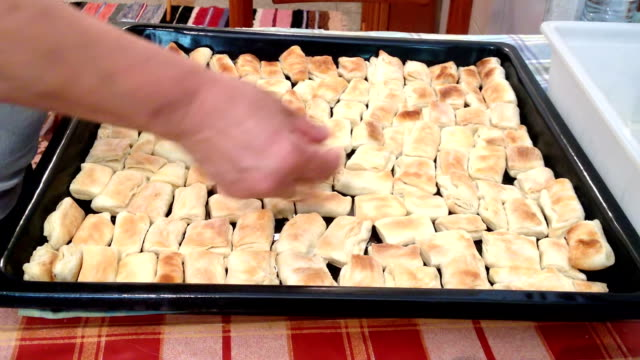woman puts baked golden puffs on the baking tray pan - baking tray stock videos & royalty-free footage