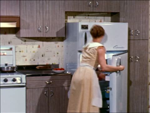 vídeos de stock e filmes b-roll de 1959 rear view pan woman puts food into refrigerator, takes food out of freezer + puts it in oven - 1950 1959