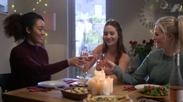 Woman puts food on the table , sits down and makes a toast with her girlfriends.