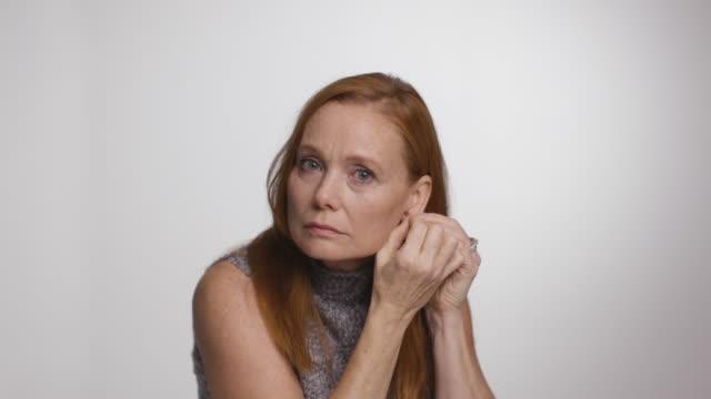 woman puts on earrings in mirror - turtleneck stock videos & royalty-free footage