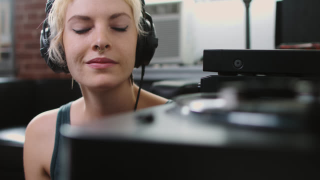 vídeos y material grabado en eventos de stock de mujer se pone auriculares y cierra los ojos - auriculares equipo de música