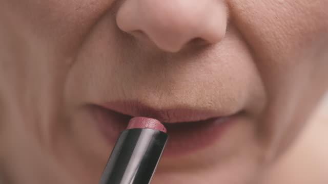 Woman Puts on Lip Gloss in Mirror