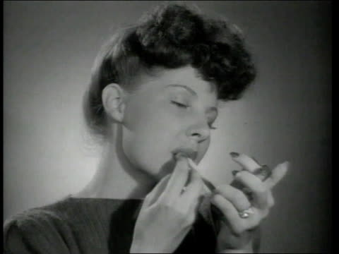 1942 montage woman puts on lipstick using compact mirror while smoking a cigarette at the same time - lipstick stock videos & royalty-free footage