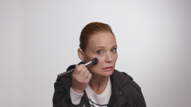 vídeos de stock, filmes e b-roll de woman puts on makeup in mirror - blush