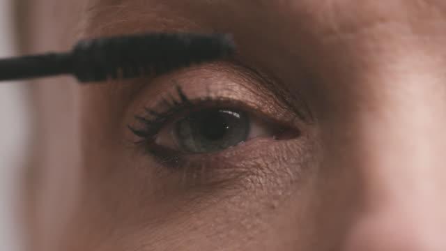 Woman Puts on Mascara in Mirror