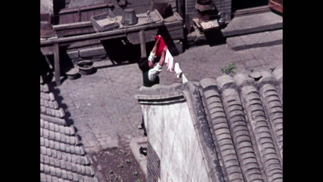woman puts out washing among grey houses in beijing; 1973 - maoism stock videos & royalty-free footage