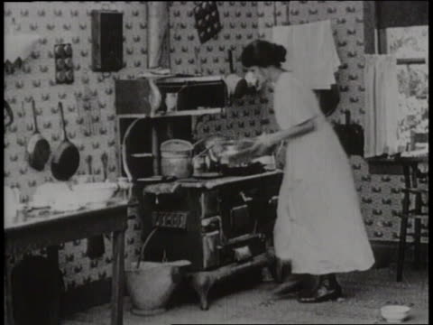 a woman puts wood in the kitchen stove and starts cooking - gender stereotypes stock videos & royalty-free footage