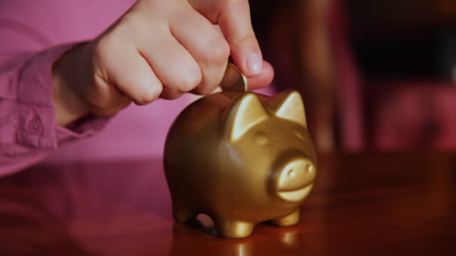 woman putting a coin in a piggy bank at home. - currency symbol stock videos & royalty-free footage
