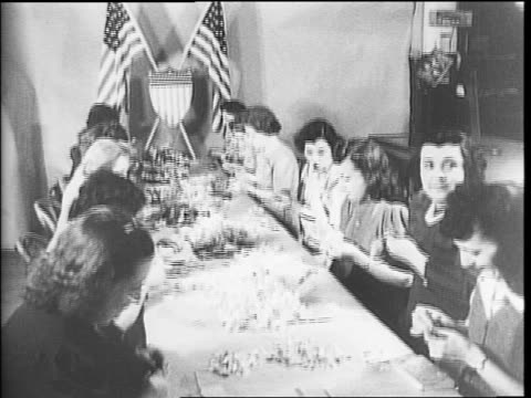 woman putting a corsage made of war stamps on to a woman's lapel / women working with a pile of stamps on a table / long table of women working /... - hair accessory stock videos & royalty-free footage