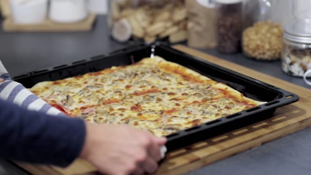 ds woman putting a tray of a homemade pizza on a table - margherita video stock e b–roll