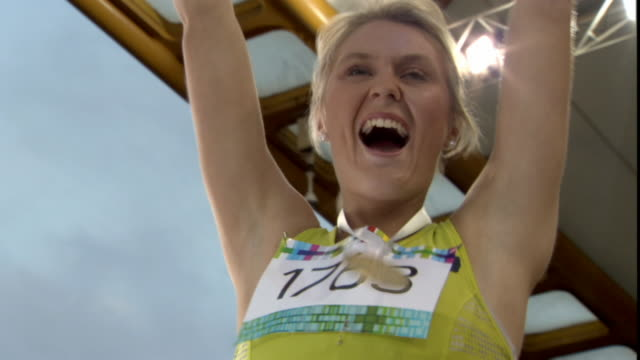 la ms woman putting arms up and blowing kisses to stadium after winning medal in track event/ women embracing and jumping up and down/ sheffield, england - medallist stock videos & royalty-free footage