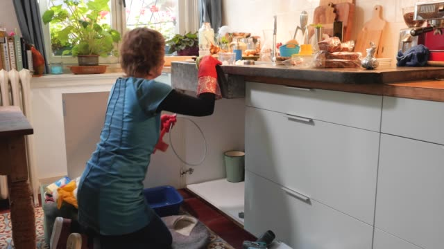 vídeos de stock e filmes b-roll de woman putting back the plumber's snake after unclogging the drain - lava loiças
