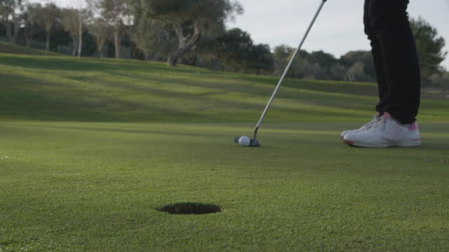 vidéos et rushes de la cu woman putting, ball rolls into hole, red r3d 4k - balle de golf