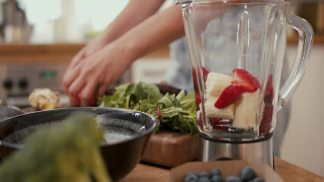 woman putting banana, strawberries and spinach in blender for smoothie at home - smoothie stock videos & royalty-free footage
