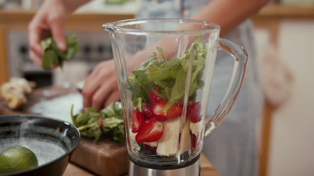 woman putting banana, strawberries, spinach and blueberries into blender at home - smoothie stock videos & royalty-free footage