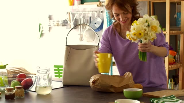 woman putting beautiful bouquet of daffodils in a vase on her kitchen counter - vase stock videos & royalty-free footage