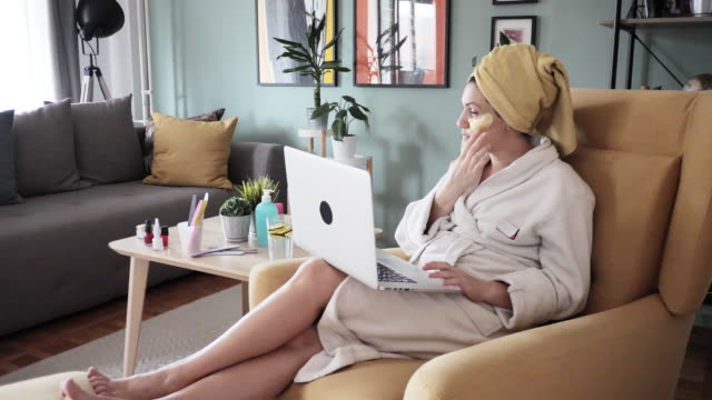 vídeos y material grabado en eventos de stock de mujer poniendo máscara de belleza y teleconferencia con amigos debido a las medidas de distanciamiento social - personas bellas