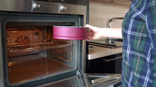 woman putting cake in the oven and setting the oven temperature - cake stock videos & royalty-free footage