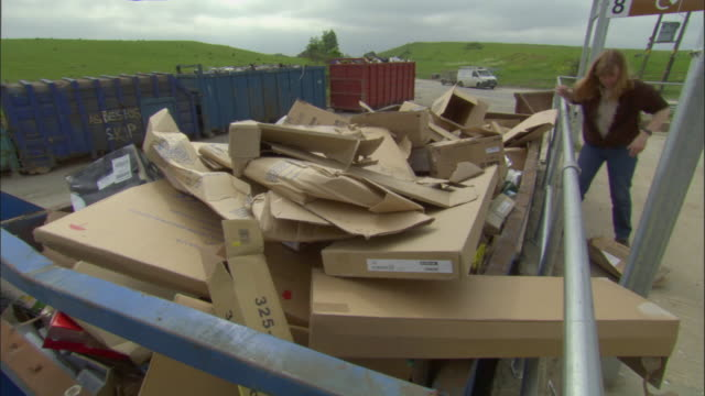 MS, Woman putting cardboard boxes into recycling bin, Ardley, Oxfordshire, United Kingdom