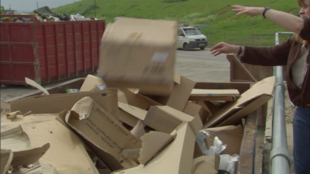 stockvideo's en b-roll-footage met cu, pan, woman putting cardboard boxes into recycling bin, ardley, oxfordshire, united kingdom - kartonnen doos
