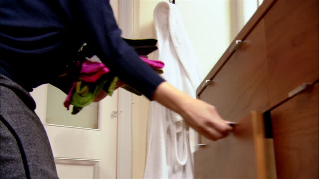 woman putting clean laundry away in bureau drawer - drawer stock videos & royalty-free footage