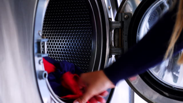 woman putting clothes in a washing machine. - waschsalon stock-videos und b-roll-filmmaterial