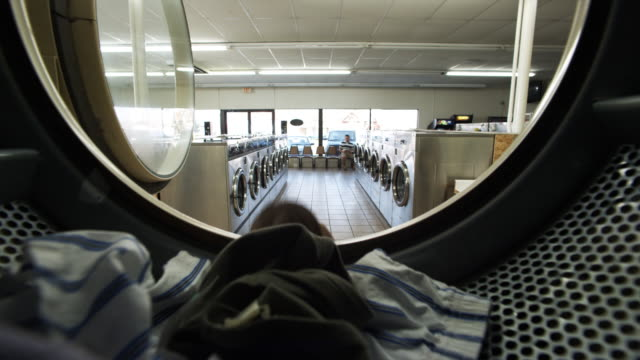 vídeos y material grabado en eventos de stock de woman putting clothes in dryer - lavandería edificio público