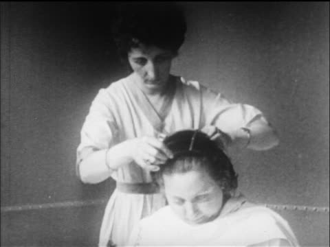 B/W 1919 woman putting comb into other woman's hair in beauty parlor / newsreel