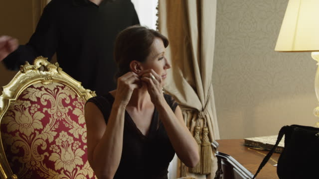 stockvideo's en b-roll-footage met ms woman putting earrings on,man approaching,kissing woman and both leaving hotel room / venice,veneto - oorbel