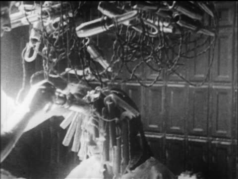 B/W 1919 woman putting electric curlers in other woman's hair in beauty parlor / newsreel