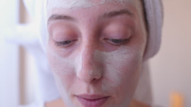 woman putting facial mask on her face - towel stock videos & royalty-free footage