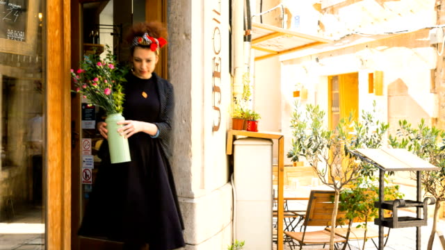 woman putting flowers at entrance of restaurant - gastwirt stock-videos und b-roll-filmmaterial